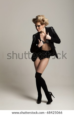 Fashion girl in a jacket and boots, bent leg - stock photo