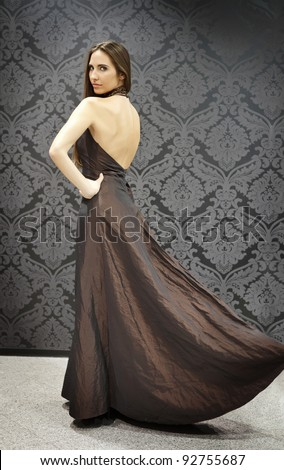 fashion girl in long marvelous dress, posing and looking at camera