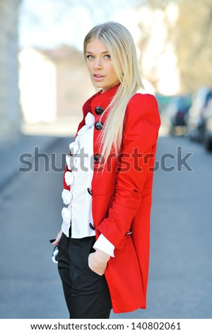 Fashion girl in red dress posing outdoors