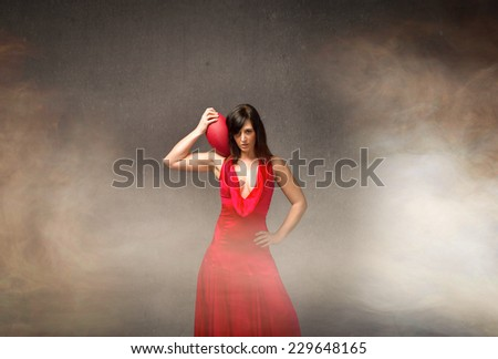 fashion girl in red dress with american football on shoulder - stock photo