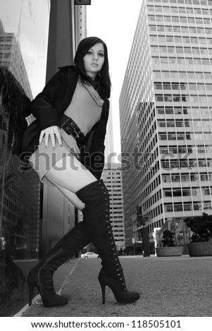 fashion girl in sexy boots posing in big city, urban outfit, black and white