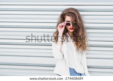 fashion girl in sunglasses. photo on the background of the fence - stock photo