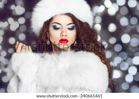 Fashion girl model posing in fur coat and white furry hat. Winter Beautiful Woman in Luxury clothes over bokeh Christmas Lights background.