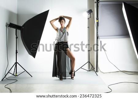 Fashion girl model posing on white background in the studio.  - stock photo
