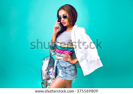 Fashion girl posing at studio, wearing smart casual sportive outfit, business style, sweet pastel colors, sunglasses, backpack denim and jacket, mint background, stylish woman. - stock photo