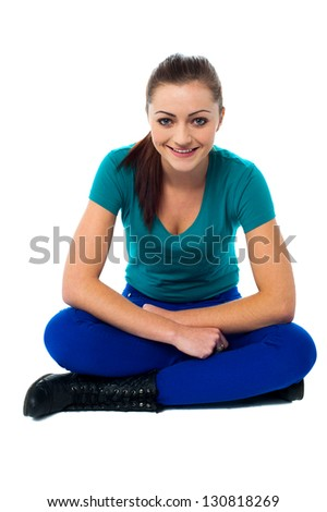 Fashion girl posing casually, sitting with legs crossed on the floor.