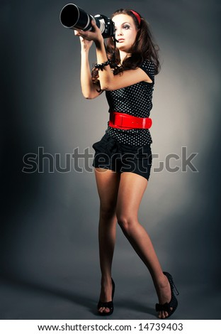 Fashion girl posing with camera on black background
