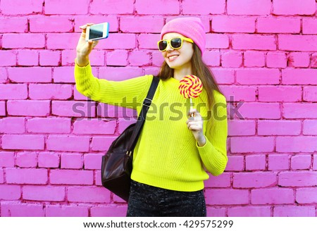 Fashion girl taking photo selfie portrait using smartphone over colorful pink background - stock photo