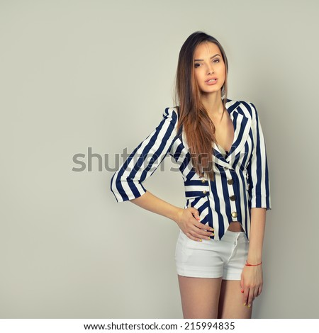 Fashion girl, toned. Young sexy brunette woman posing at studio in striped jacket and white shorts
