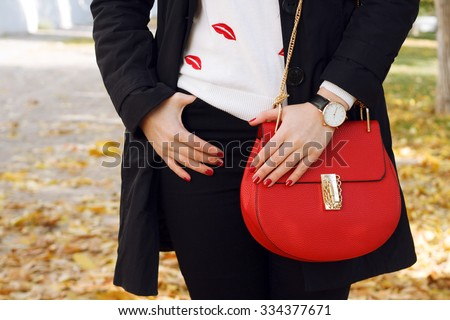 Fashion girl wearing coat ,red handbag, black jeans ,white pullover. Trendy accessories - stock photo