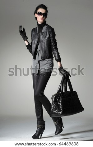 Fashion girl wearing modern sunglasses with bag posing in the studio