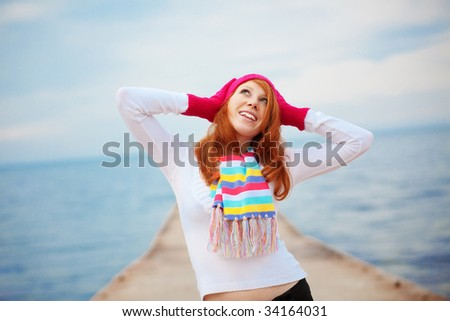 Fashion girl wearing spring clothing on a berth near the sea - stock photo