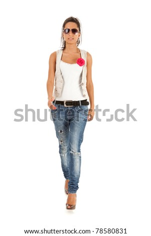 Fashion girl wearing sunglasses and  jeans  walking in studio - stock photo