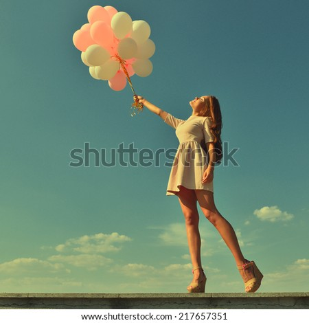 Fashion girl with  air balloons over blue sky, image toned. - stock photo