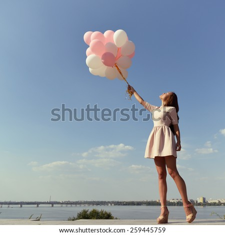 Fashion girl with  air balloons over blue sky, toned - stock photo