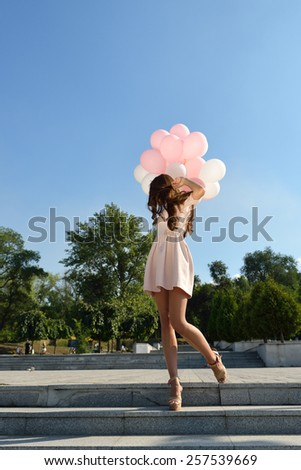 Fashion girl with air balloons steps on stairs - stock photo