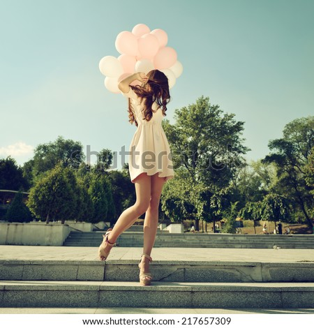 Fashion girl with air balloons steps on stairs, image toned. - stock photo