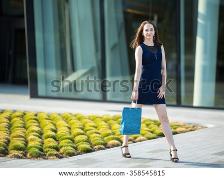 Fashion girl with bag in hand on the street. - stock photo