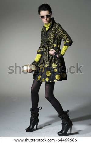 Fashion girl with bag posing in the studio - stock photo