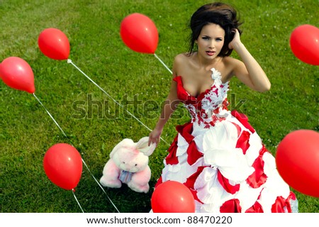 Fashion girl with baloon on grass background