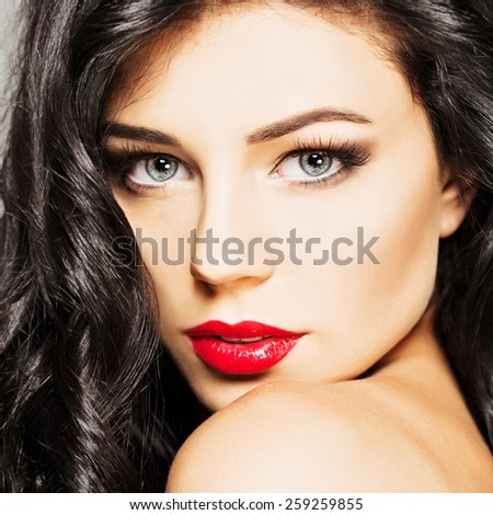Fashion girl with curly hair and makeup, face closeup - stock photo