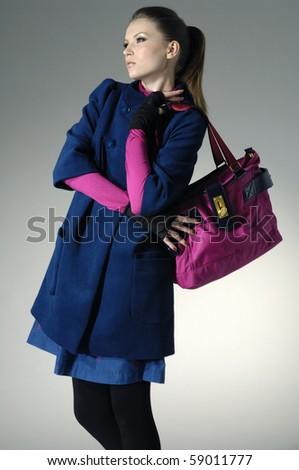 Fashion girl with handbag posing in light background - stock photo