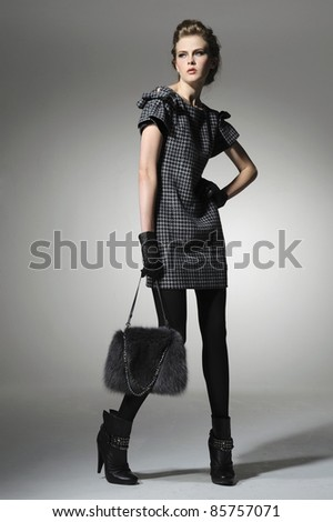 Fashion girl with handbag posing in light background - stock photo