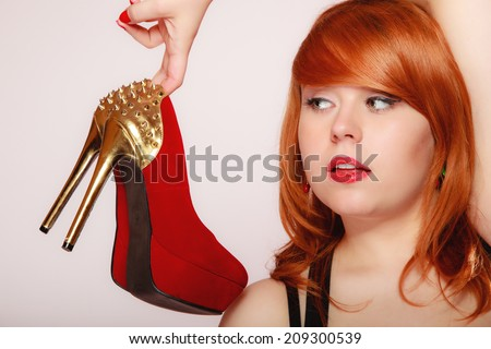 Fashion girl with red high heel shoes stiletto boots with gold studs. Women loves shoes concept - stock photo