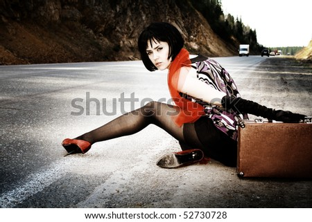 Fashion girl with suitcase stops the car on road - stock photo