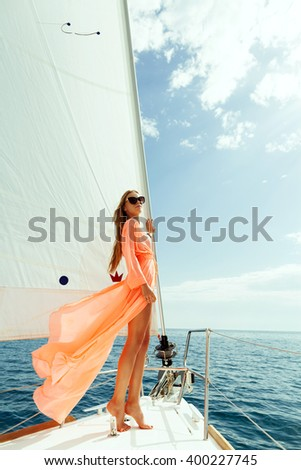 fashion girl yachting in sea with sarong and blue sky sunlight