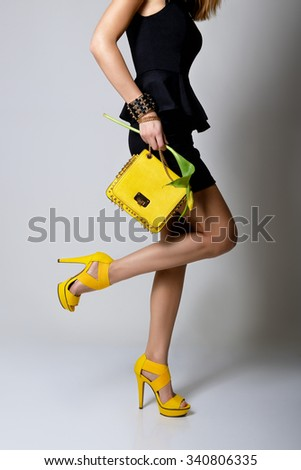 Fashion girl. Young woman posing in black dress and yellow handlbag and shoes - stock photo
