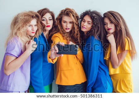 Fashion girls in bright clothes make selfie. Beautiful women with professional makeup and crazy hair style, over white background.
