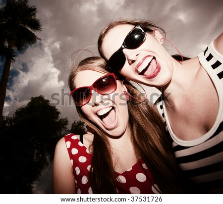Fashion Girls on a Stormy Day Against Cloudy Sky - stock photo