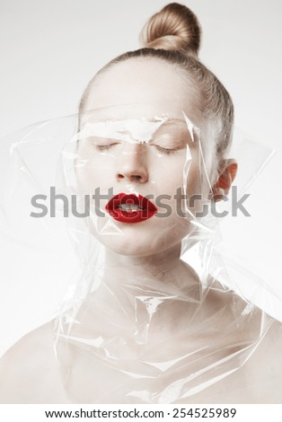 Fashion.glamor closeup portrait of beautiful sexy blonde model with bright makeup, with red lips, with perfect clean skin in studio, with transparent paper  - stock photo