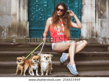 fashion glamor girl with dog  in sunglasses sitting in the old town, vintage - stock photo