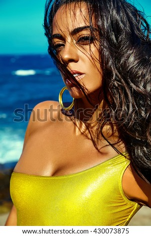 Fashion glamor portrait of beautiful sexy Caucasian hot brunette girl model with perfect sunbathed clean skin with jewelery outdoors in vogue style posing on blue ocean and sky background - stock photo