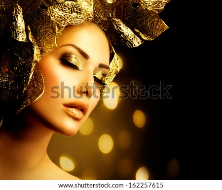 Fashion Glamour Makeup. Beauty Model Girl with Glamor Golden Make-up and Hairstyle. Holiday Gold Makeup and Hair with Floral Design over Black Background - stock photo