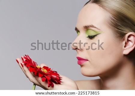 fashion glamour portrait of a blonde woman with heavy makeup holding a red gerbera flower