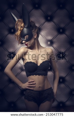 fashion glamour shoot of cute woman with perfect body wearing sexy lace lingerie and bizarre black bunny mask. Dark Easter  - stock photo