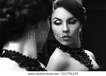 Fashion glamour woman portrait looking at mirror in vintage style with black jewellery, retro hairstyle and make-up.