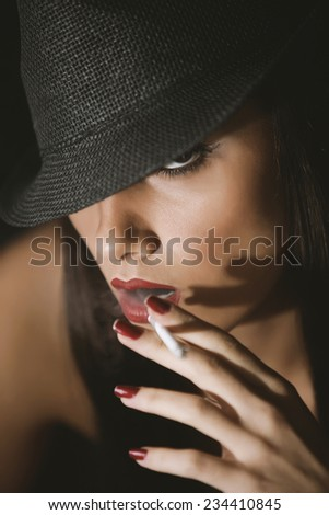 Fashion glamour woman smoking, with a cigarette and a hat - stock photo
