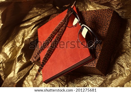 Fashion glasses and brown speckled feathers on leather notebook and retro box with leopard print on gold background. Studio shot - stock photo