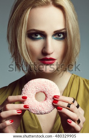 Fashion & Gluttony Concept. Portrait of luxurious blonde model in mustard cocktail dress eating pink donut over gray background. Perfect hair, skin, make-up, manicure. Golden accessories. Close up