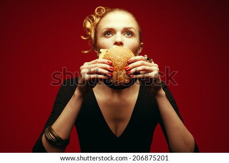 Fashion & Gluttony Concept. Portrait of luxurious red-haired model in black cocktail dress eating burger over red background. Funny curls, perfect skin, manicure. Golden accessories. Studio shot - stock photo