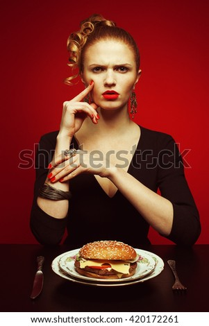Fashion & Gluttony Concept. Portrait of luxurious red-haired model in black cocktail dress eating burger over red background. Perfect hair, skin, make-up, manicure. Golden accessories. Funny pigtail - stock photo