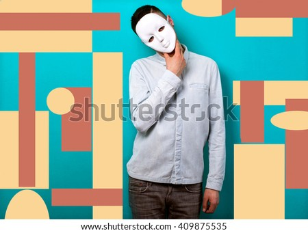 fashion guy in studio in the face mask on the background of geometric shapes - stock photo