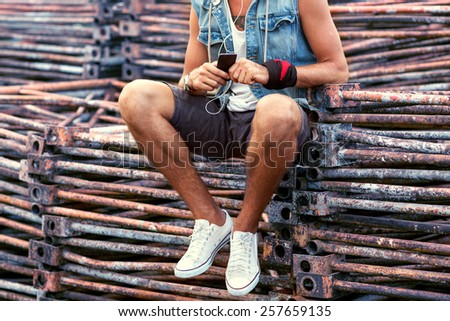 fashion guy sitting on a rusty iron retro wall, listening to the player, hipster style - stock photo
