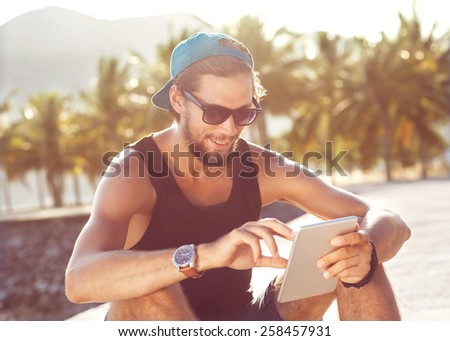 fashion guy sitting on the tablet, running in sunglasses on the beach with views of the mountains - stock photo