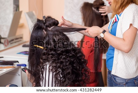Fashion hairdresser doing hairstyle to young woman making perm professional styler for curl on the background of a professional hairdressing salon. - stock photo