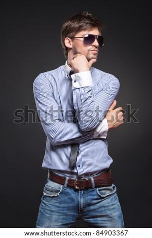 Fashion handsome man posing over black background - stock photo